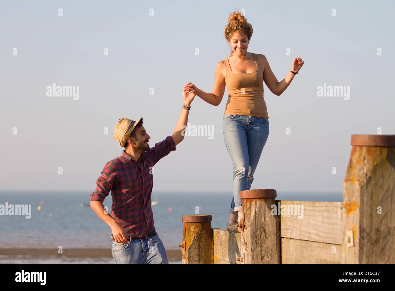 Young woman balancing on groynes holding man's hand - Stock Image