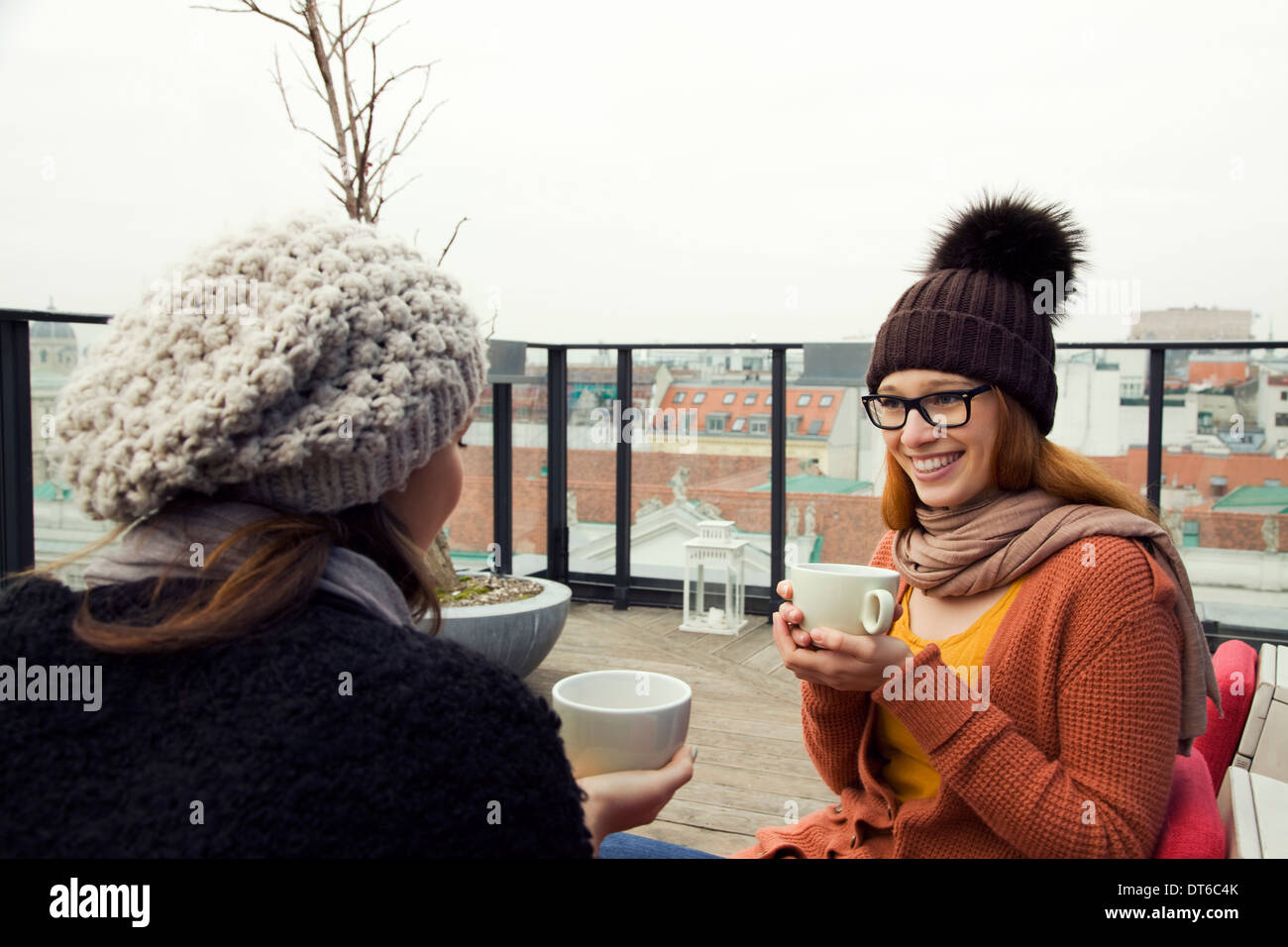 Two young adult women having coffee on rooftop terrace - Stock Image