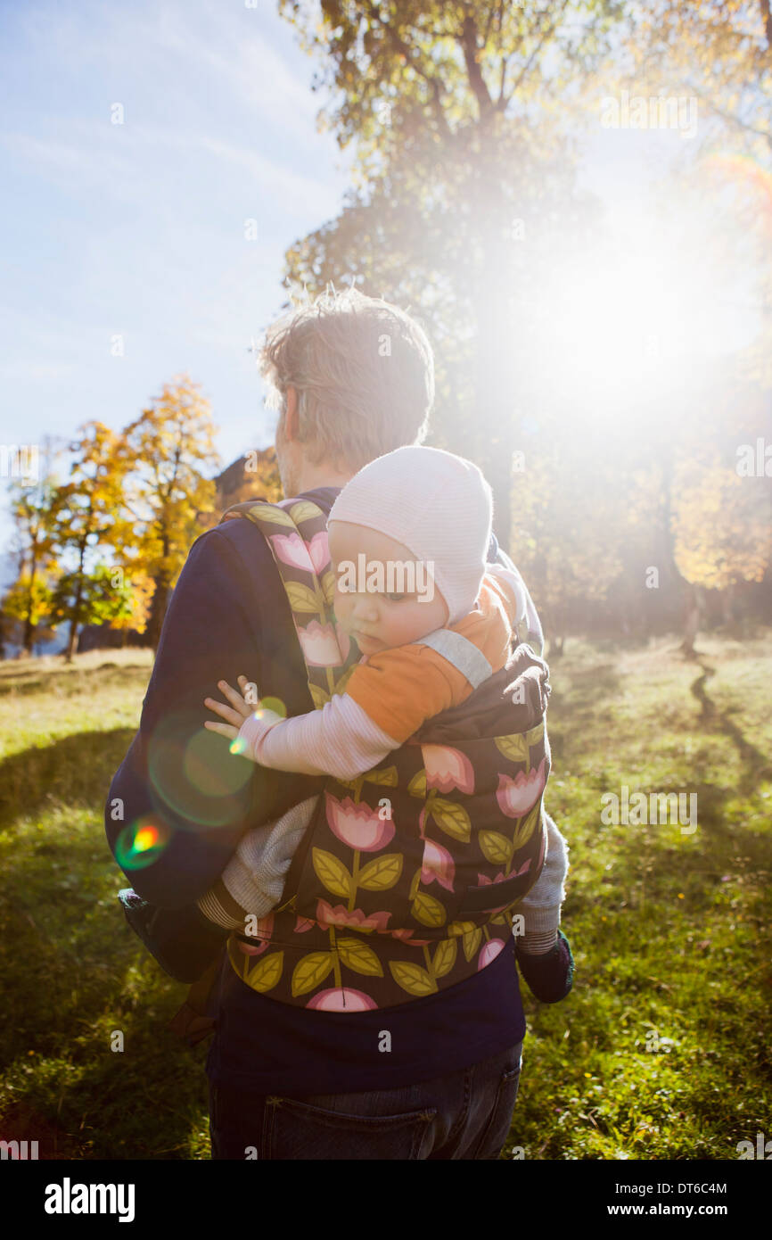 Father carrying baby daughter in carrier - Stock Image