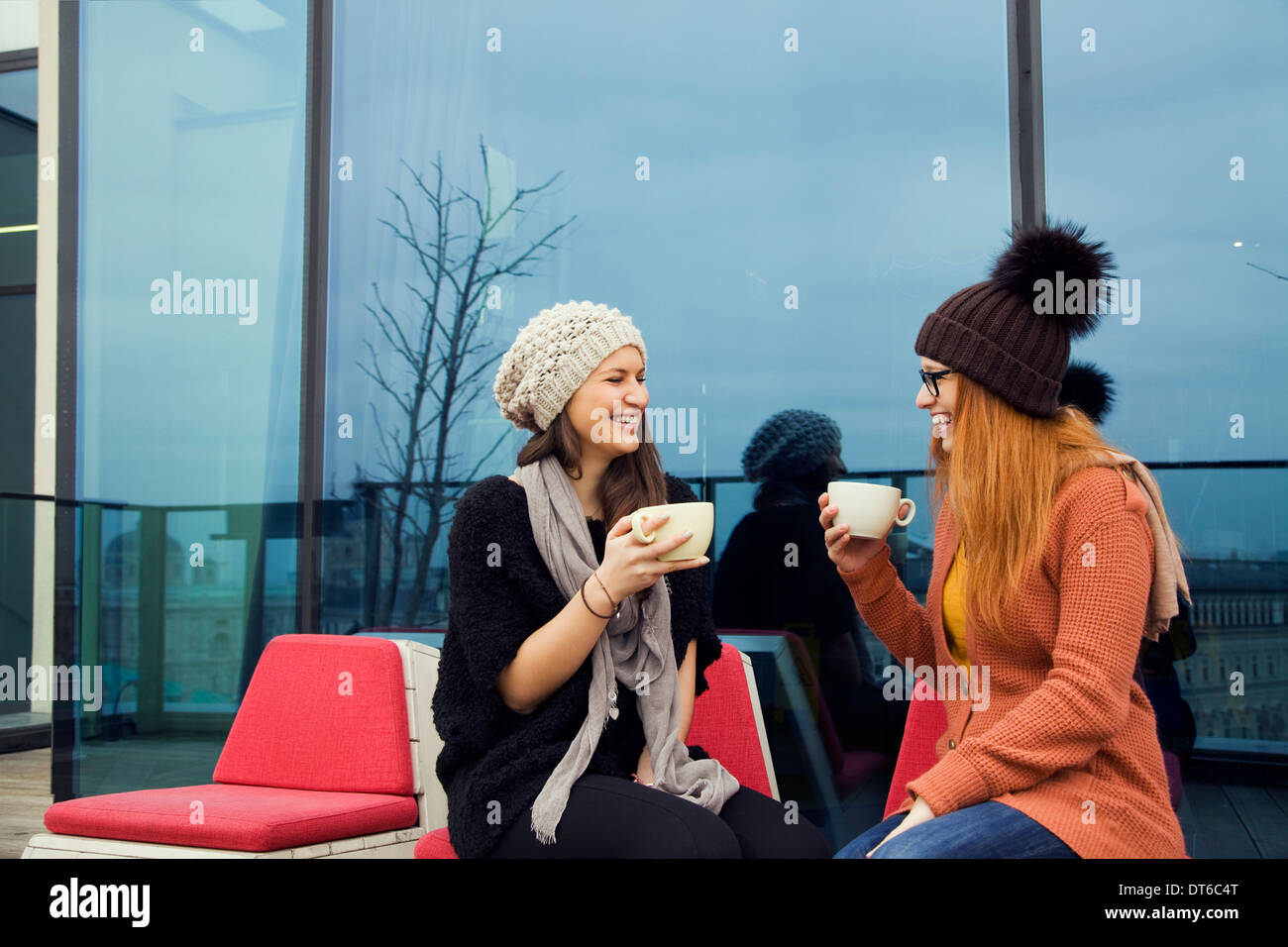 Two young adult women enjoying coffee on rooftop terrace - Stock Image