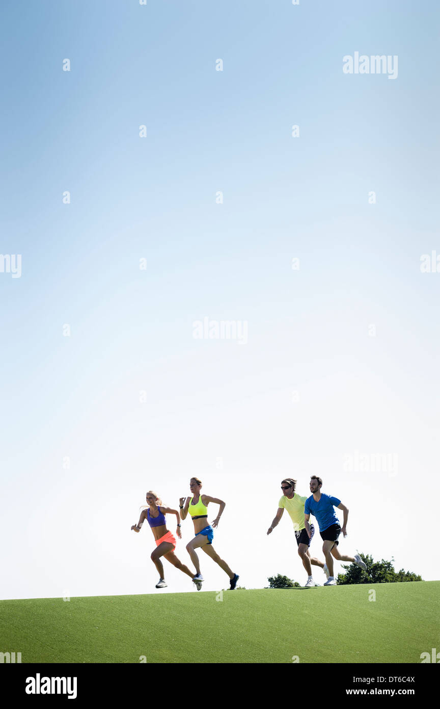 Group of adult runners running in park - Stock Image