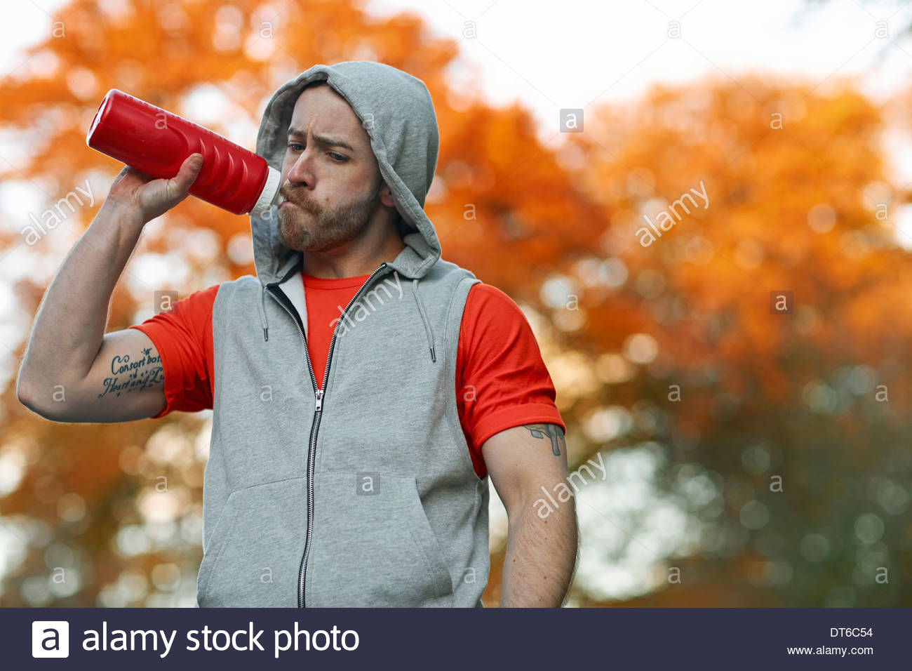 Young man drinking from plastic bottle - Stock Image