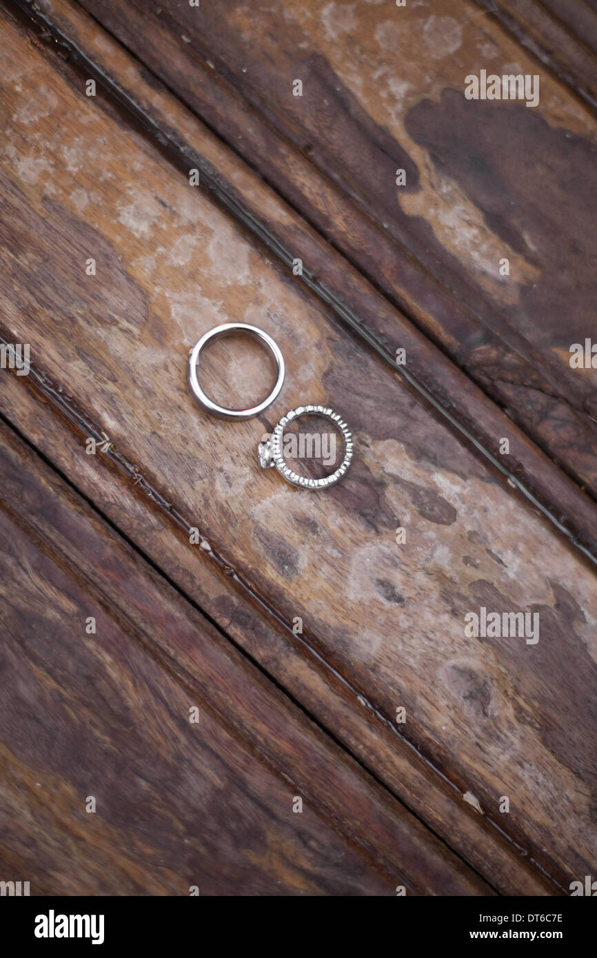 Platinum wedding rings . Two rings on a worn scrubbed stained wooden surface. - Stock Image