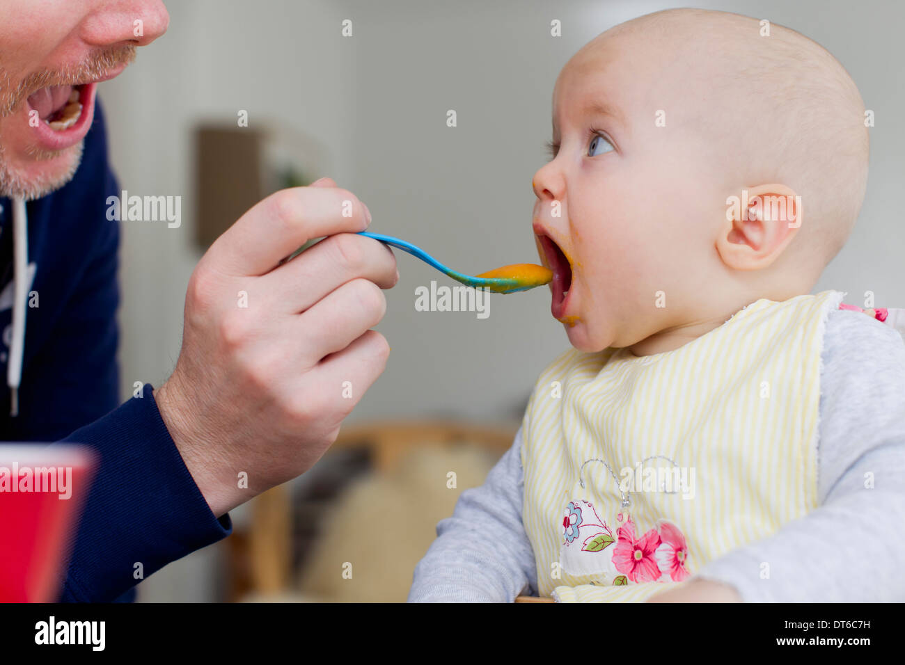 Father spoon feeding baby daughter - Stock Image