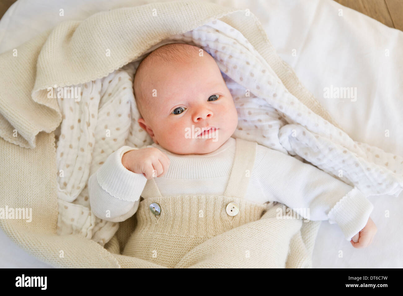 Baby girl lying on bedclothes - Stock Image