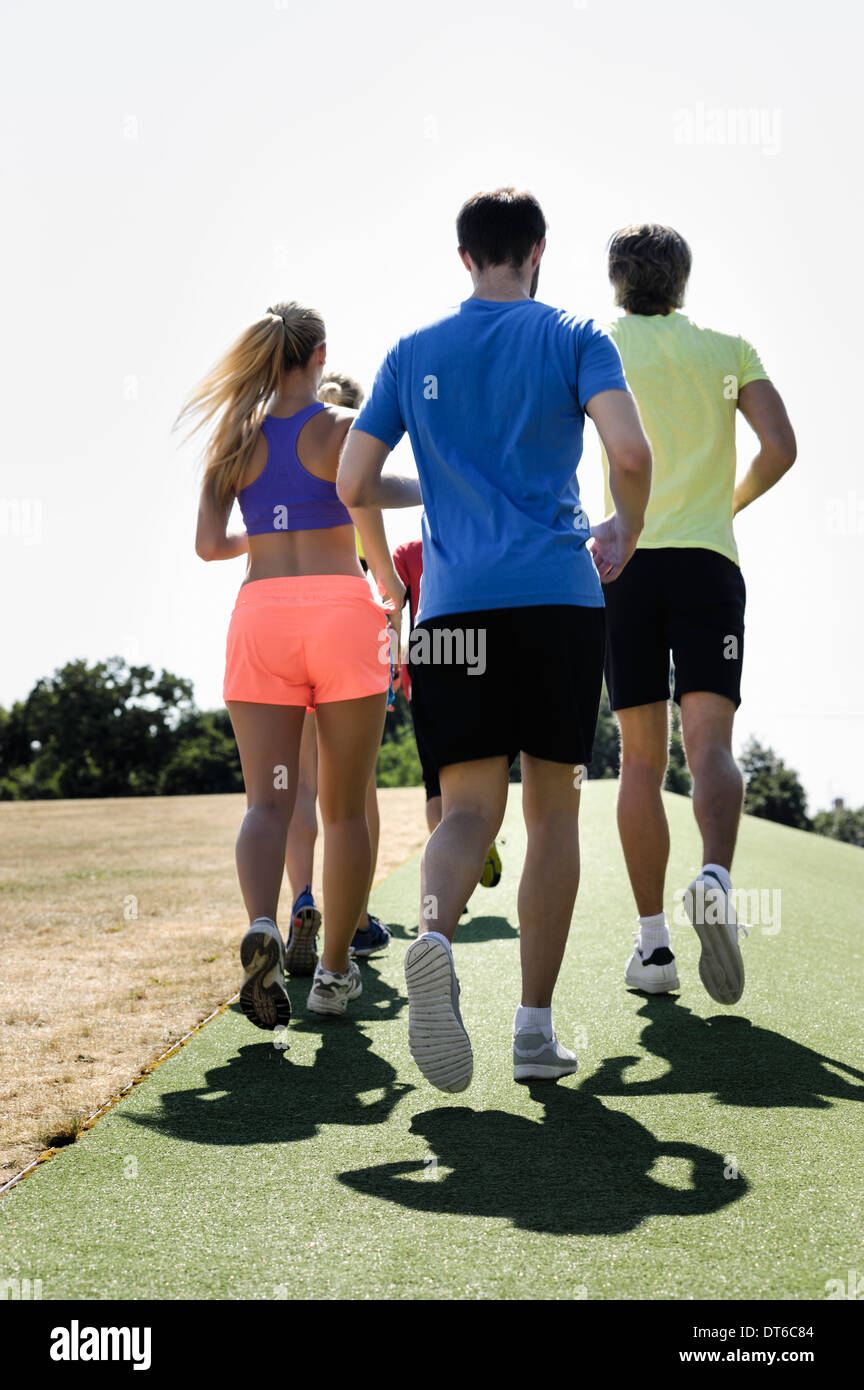 Mature trainer running with group of adults in park - Stock Image