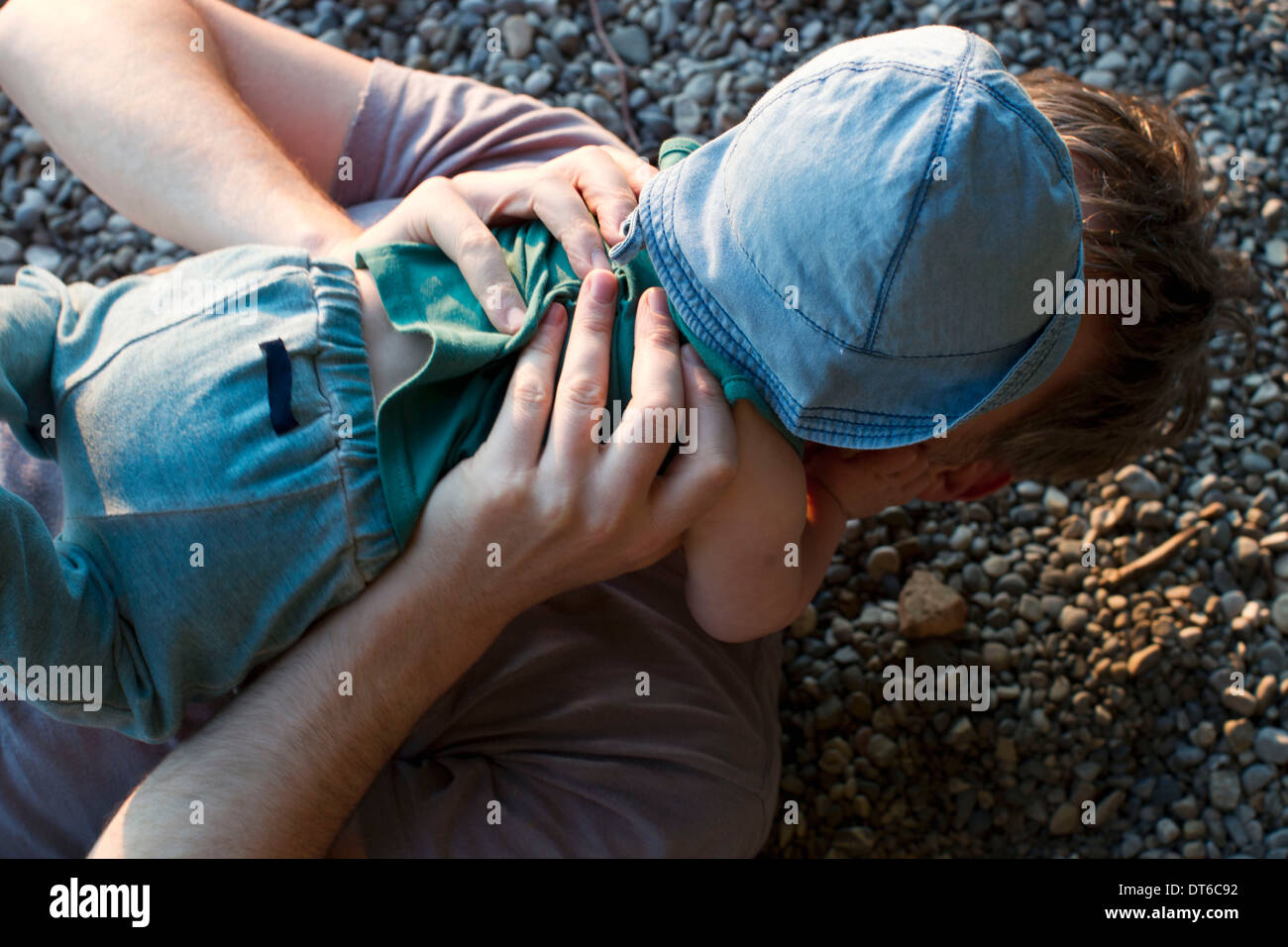 Father lying on ground holding baby daughter Stock Photo