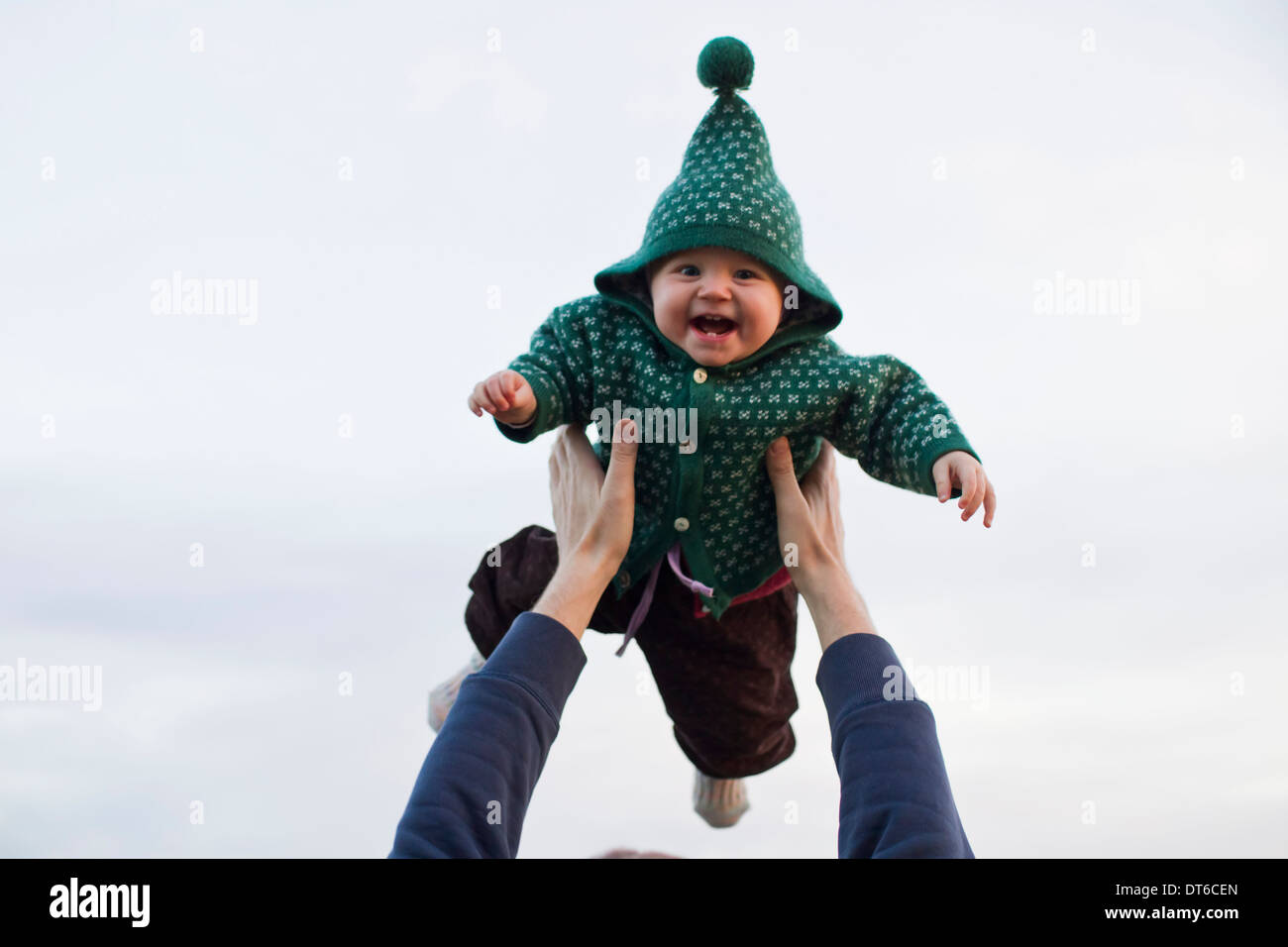 Father lifting baby daughter against sky - Stock Image