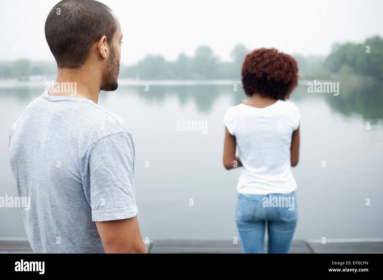 Portrait of young couple by lake, rear view - Stock Image
