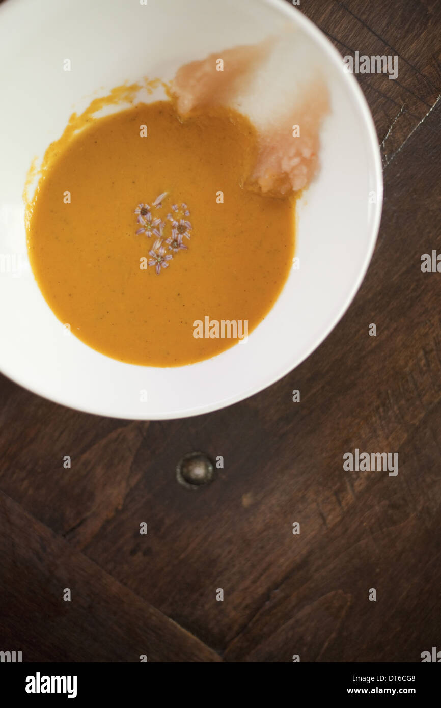 A white china bowl with a creamy soup and garnish, viewed from above. A rouille puree on the side of the dish. - Stock Image