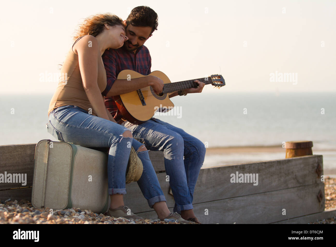 Young couple on beach, man playing guitar Stock Photo
