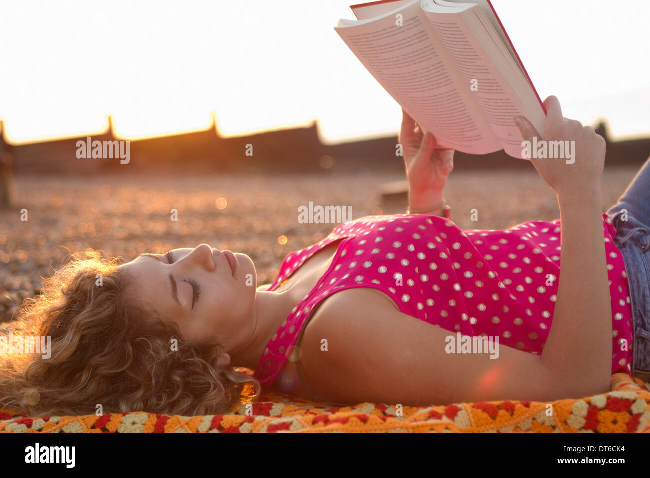Young woman lying on beach reading book - Stock Image
