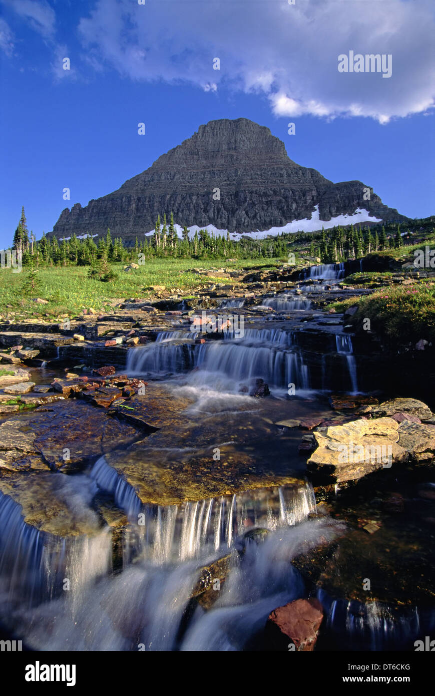 The landscape of Glacier National Park, to Mount Reynolds peak, and Logan Pass. Water flowing over rocks. - Stock Image