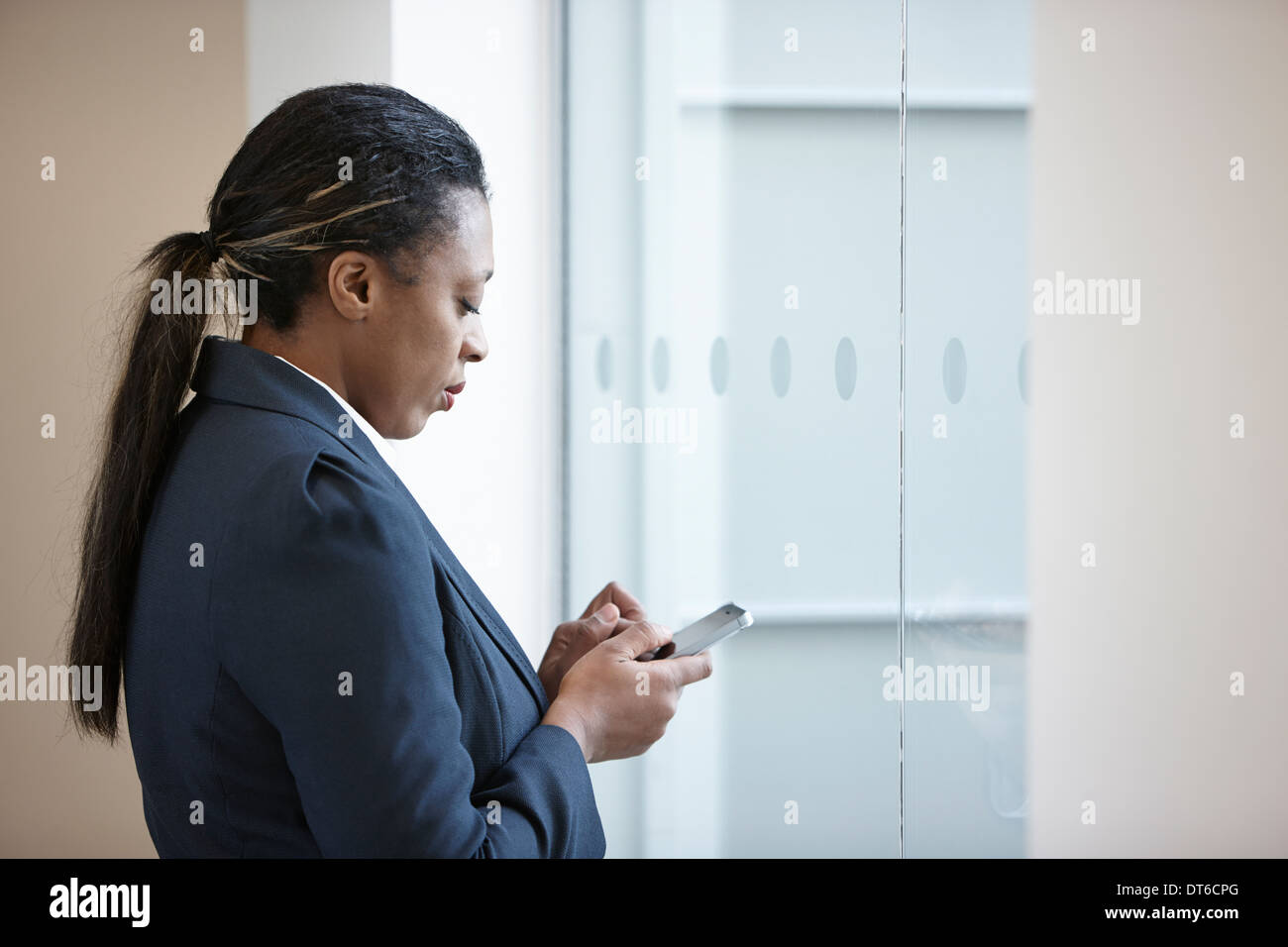 Businesswoman using cell phone - Stock Image