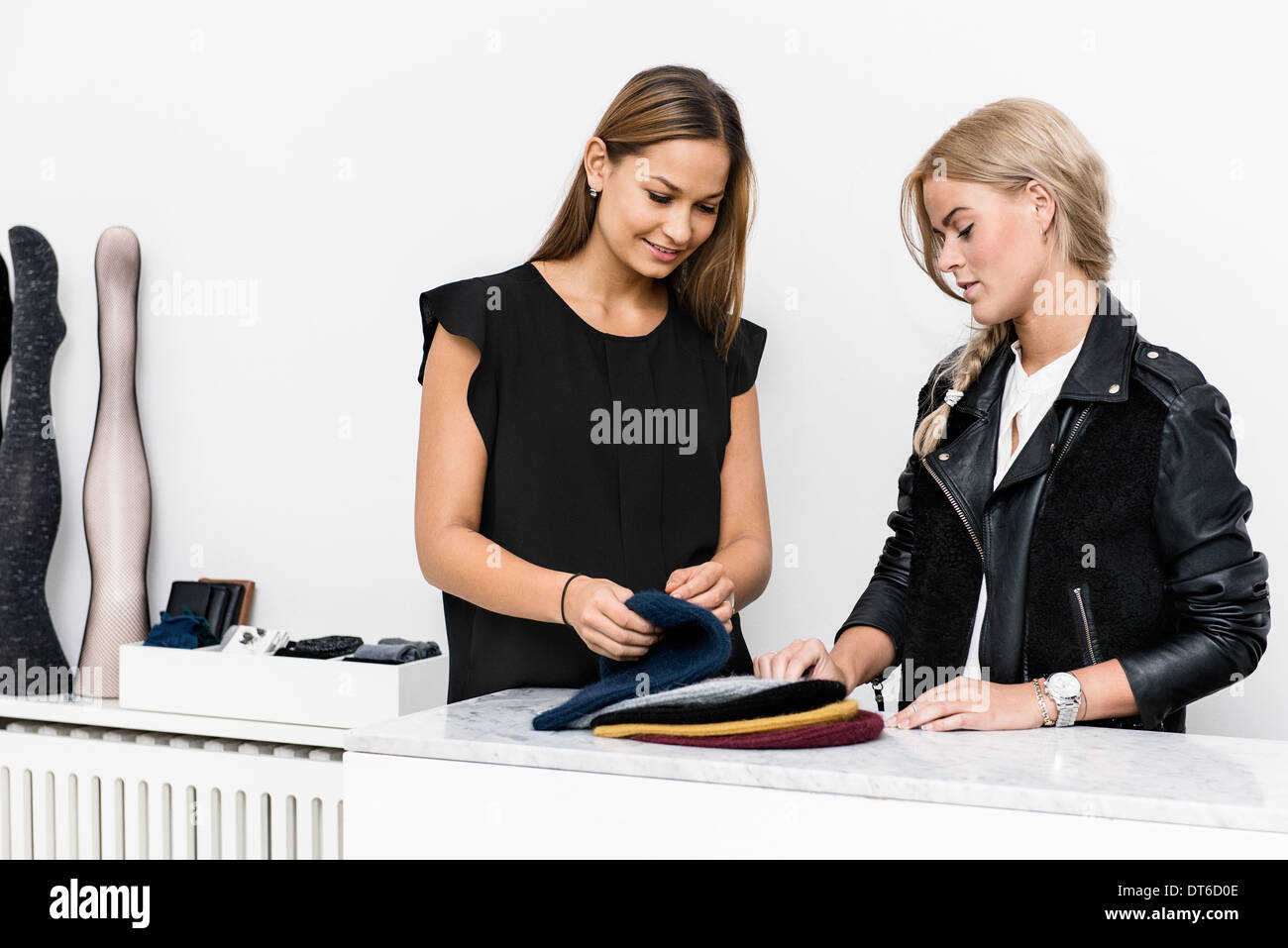 Female colleagues examining beanie hats - Stock Image