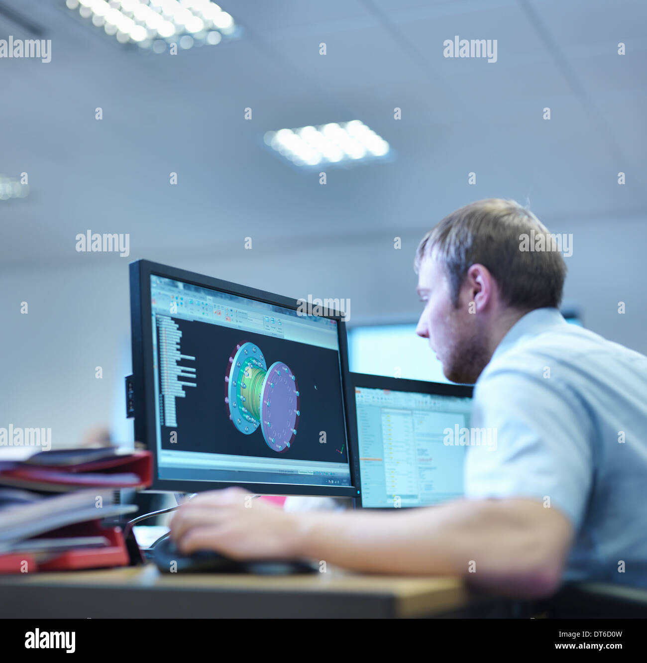 Engineer using computer aided design in factory office - Stock Image