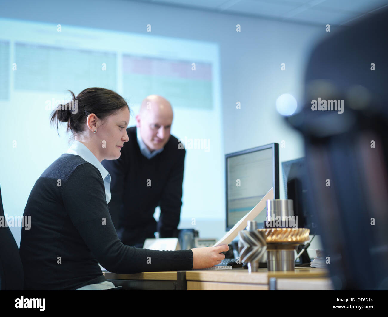 Engineers using computer aided design in factory office - Stock Image