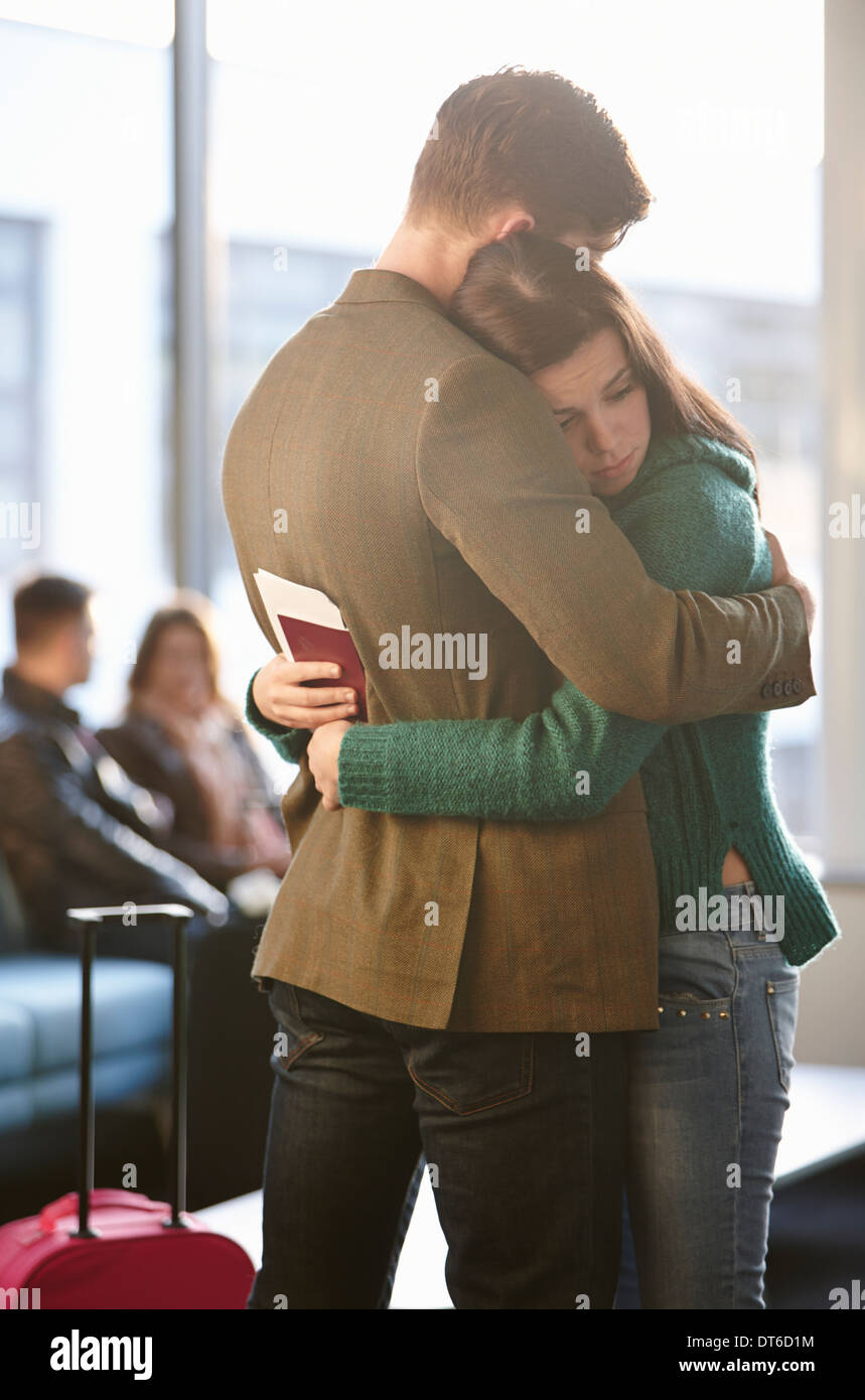 Young couple hugging in airport - Stock Image