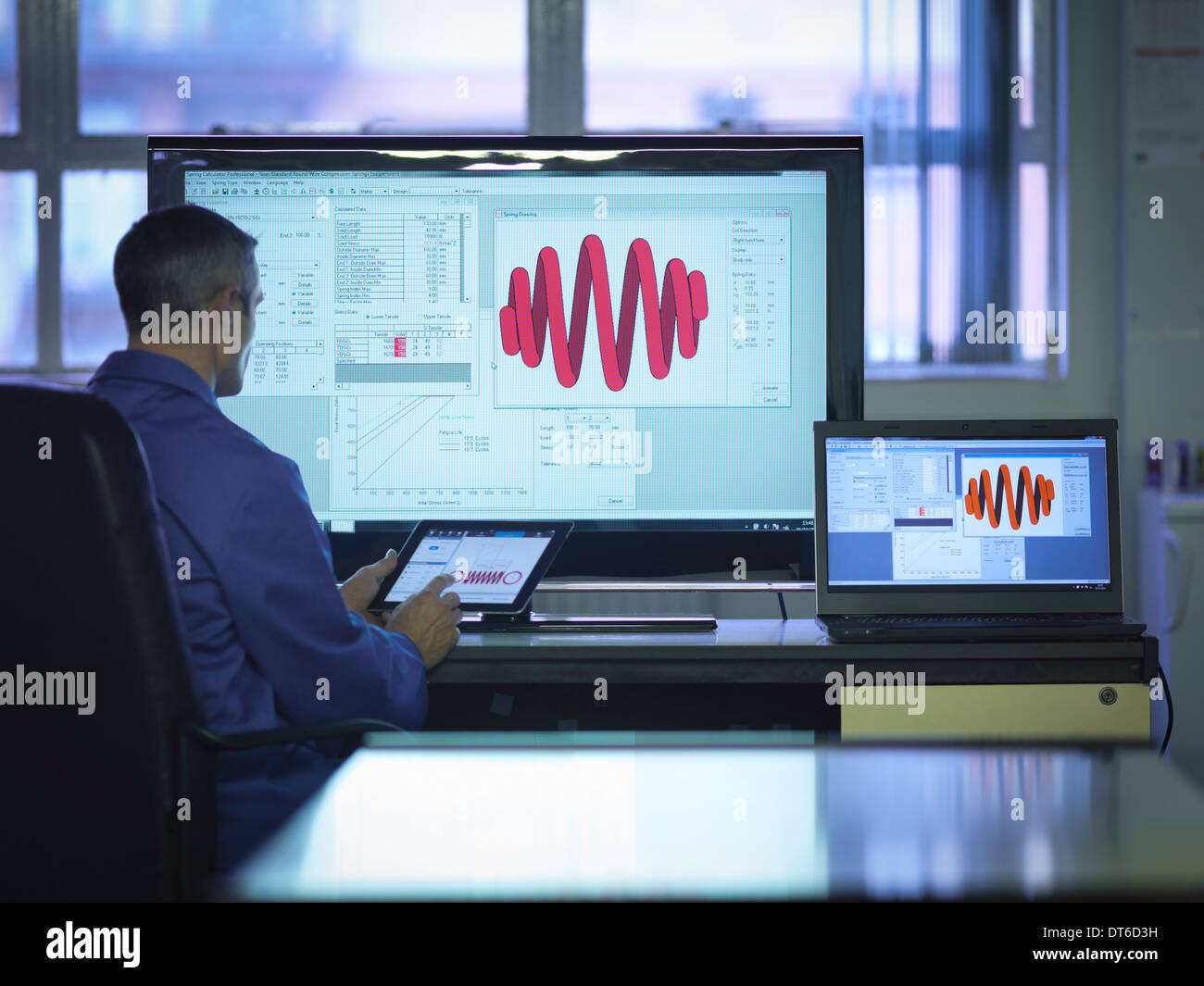 Worker using software to calibrate springs in office - Stock Image