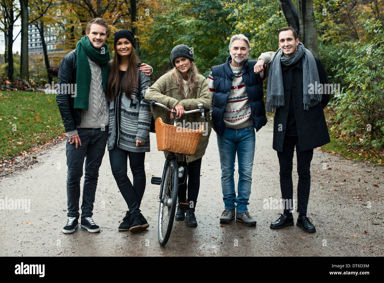 Friends posing with bicycle in woods - Stock Image