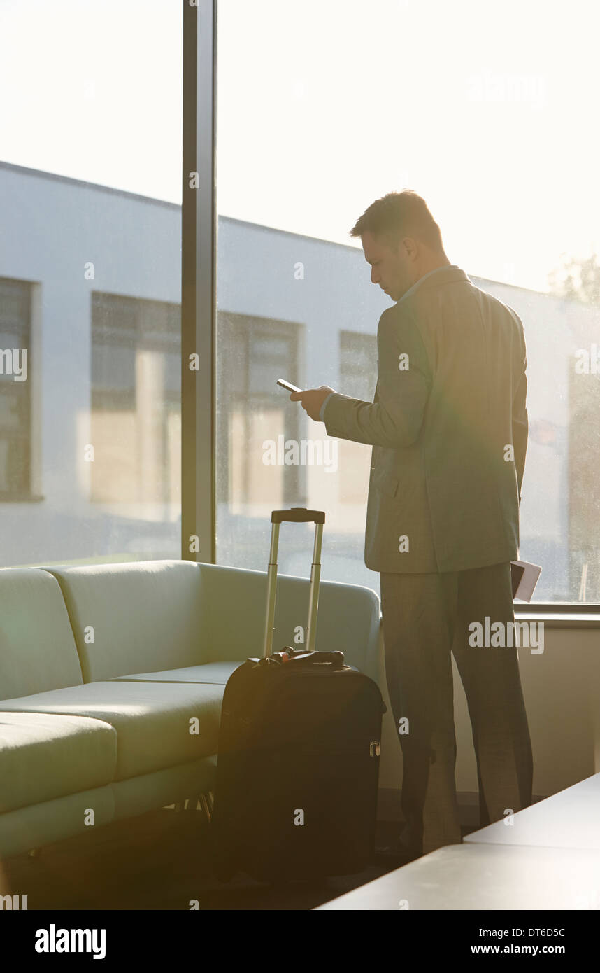 Mature man in airport using cell phone - Stock Image