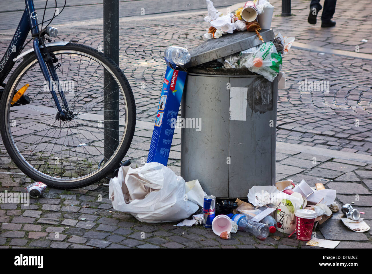 Overfull rubbish bin with trash around and garbage piled on top in city street Stock Photo