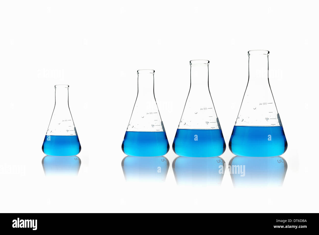 Conical glass scientific flasks holding blue liquids. Lined up in size order, with one set apart. - Stock Image