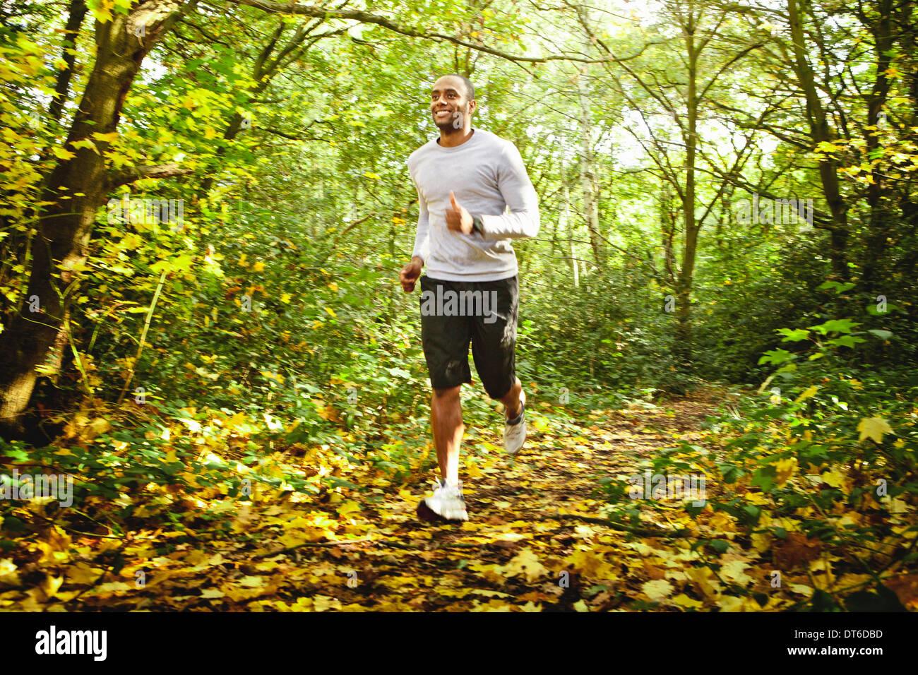 Man jogging in woods - Stock Image