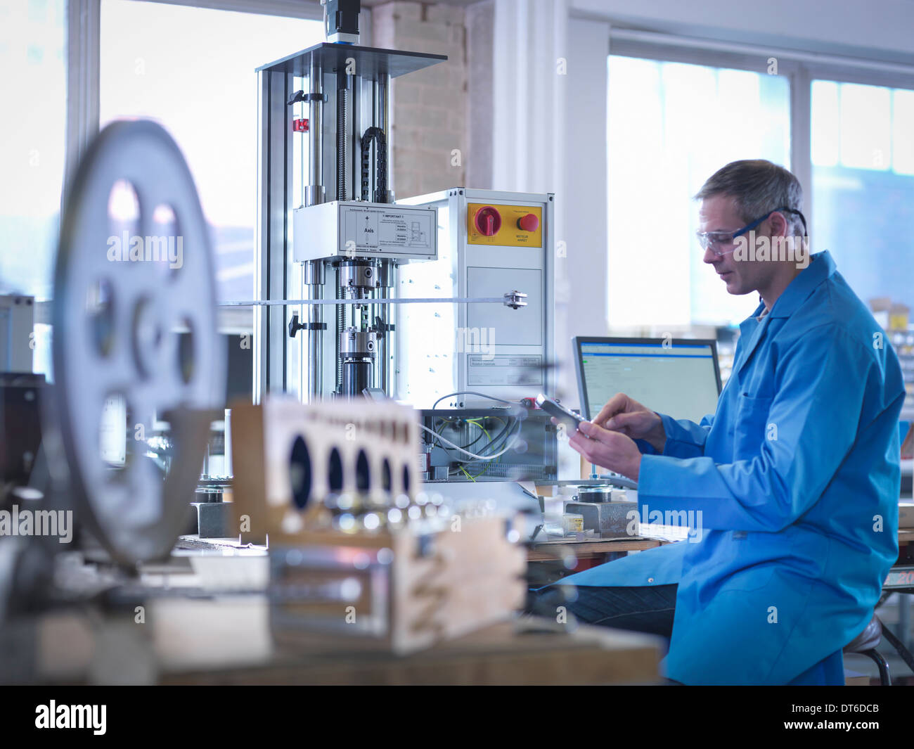 Worker in protective eyewear using spring testing equipment for automotive use - Stock Image