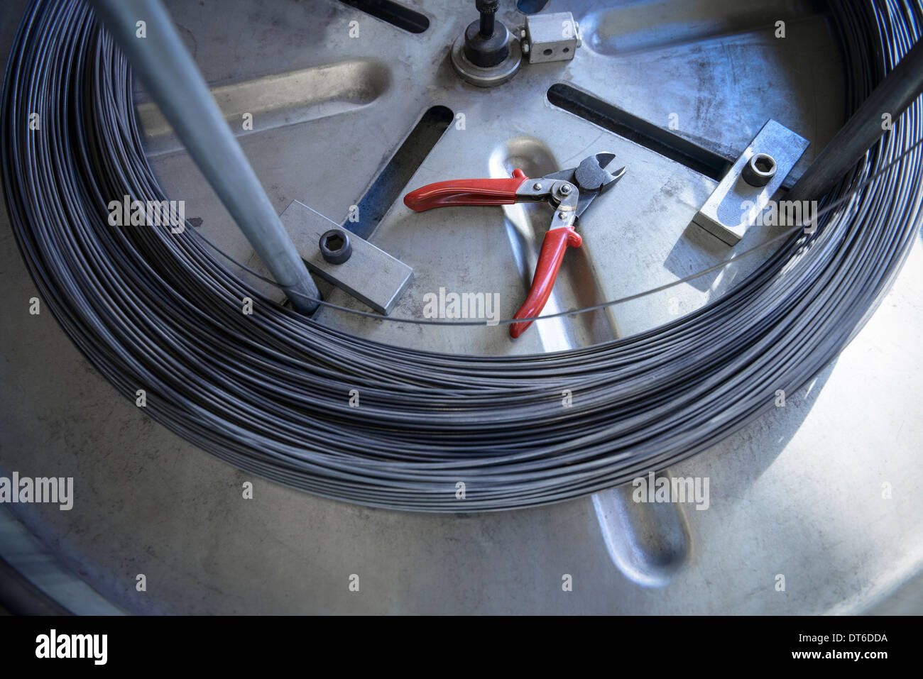 Coil of wire and wire cutters in factory - Stock Image