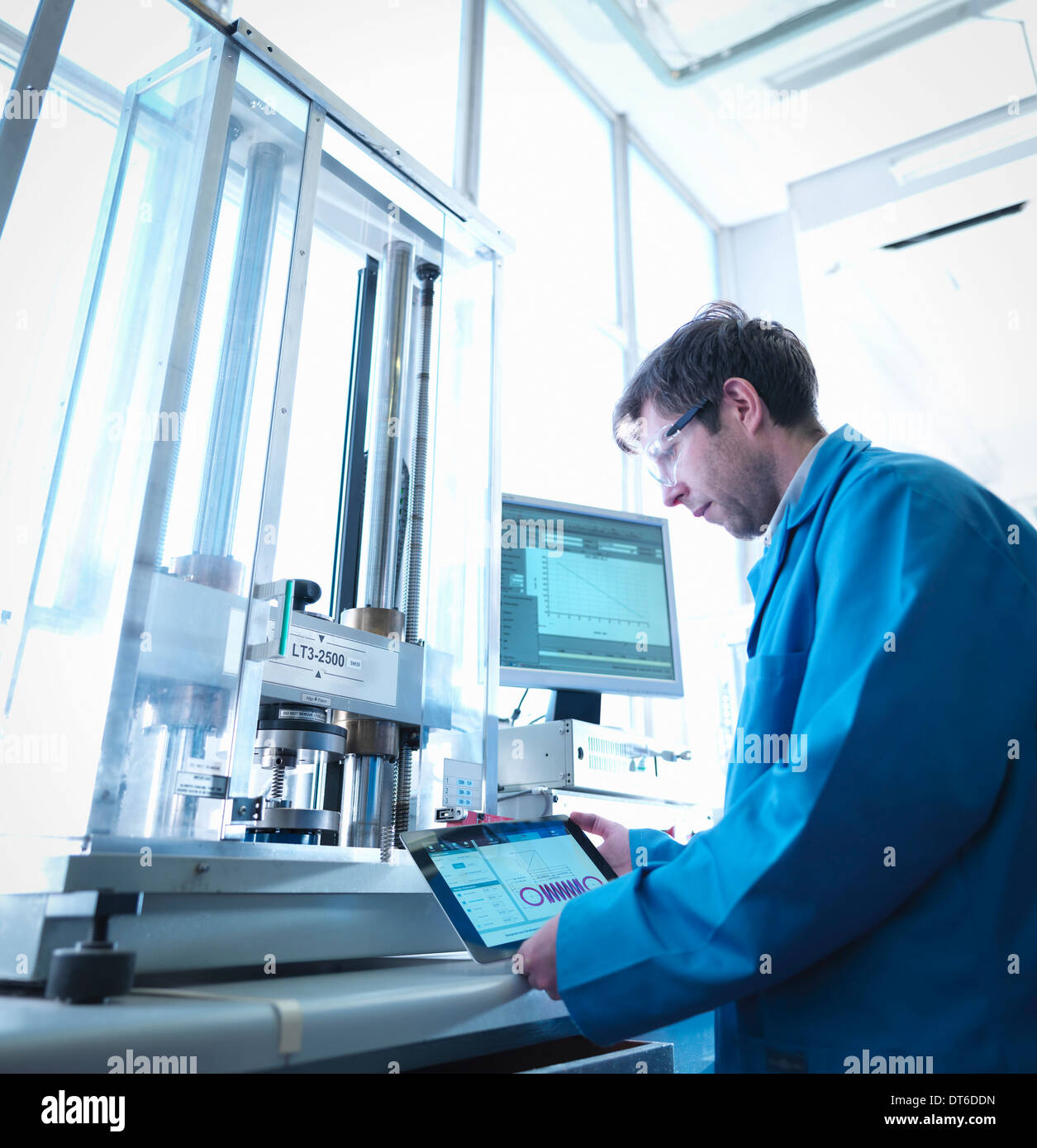 Worker using digital tablet to test spring in laboratory - Stock Image