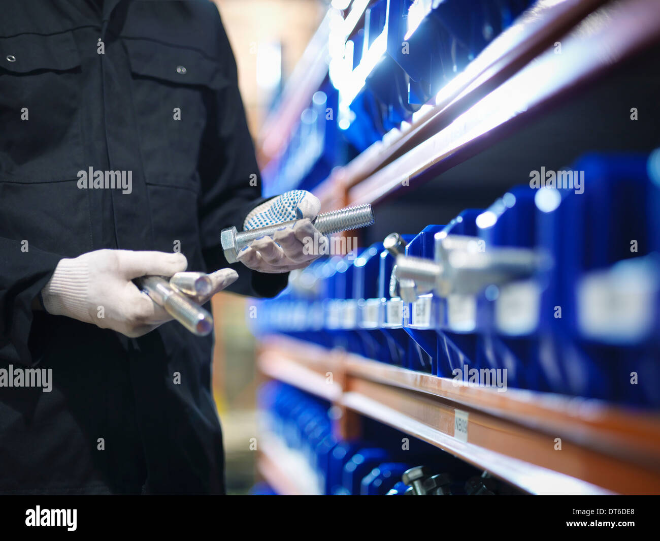 Engineer selecting bolts from store in engineering factory, close up - Stock Image