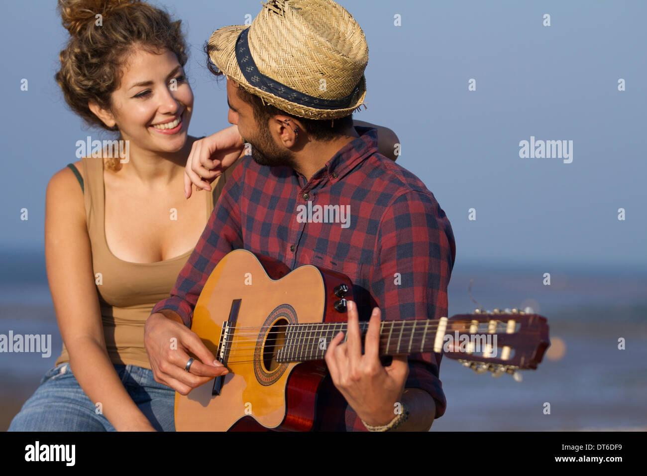 Young couple, man playing guitar - Stock Image
