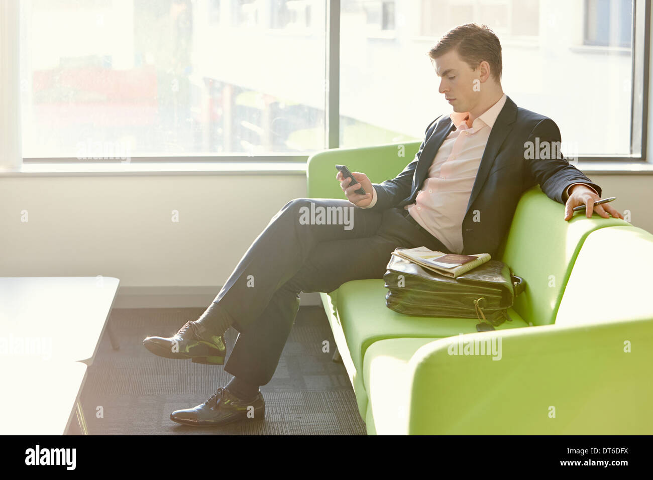 Businessman in departure lounge using cell phone Stock Photo