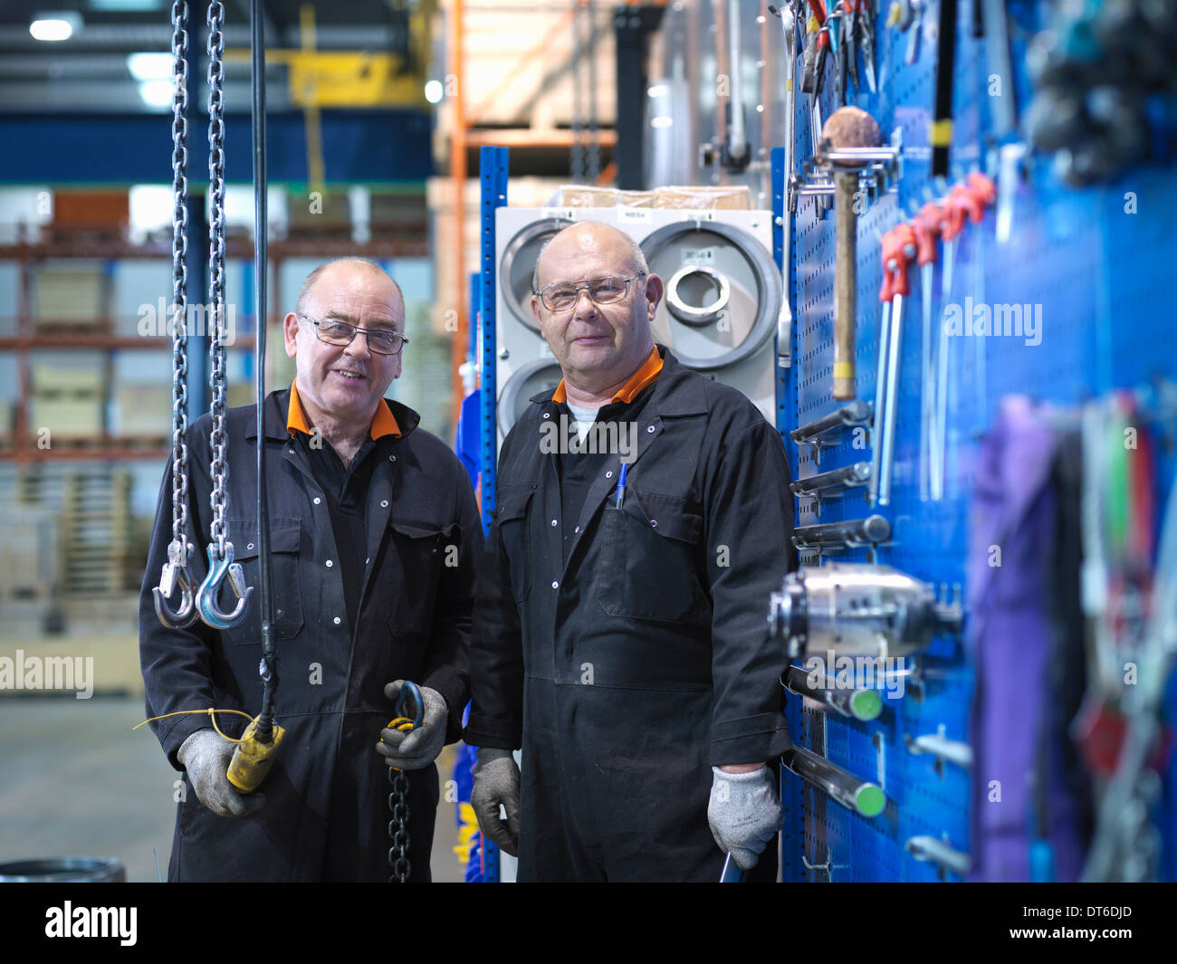 Mature engineers working in engineering factory, portrait - Stock Image