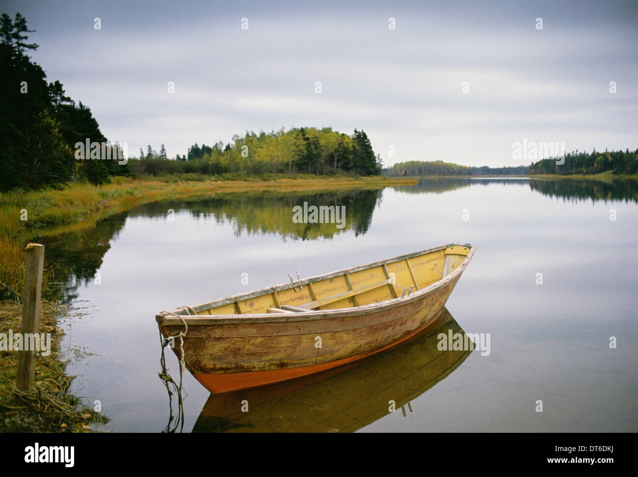 A small wooden dory or rowing boat moored on flat calm water, in Savage harbour on Prince Edward Island in Canada. - Stock Image