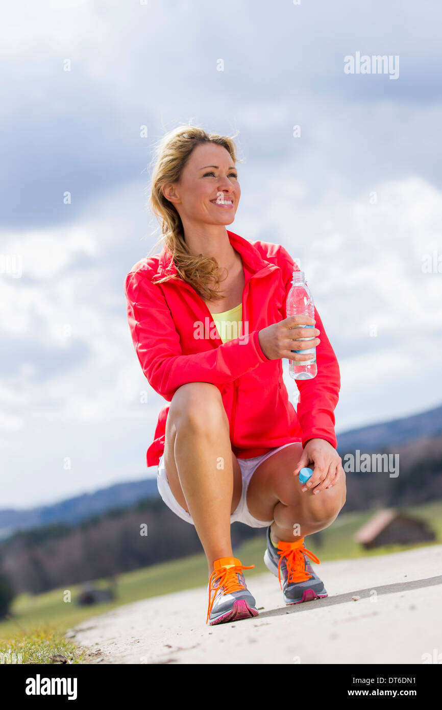 Mid adult woman with bottle of water - Stock Image