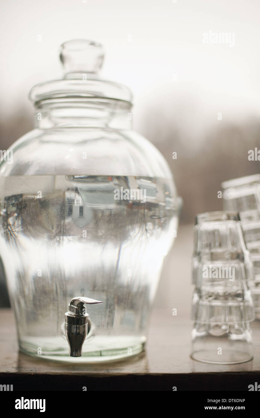 Drinking water in a large clear glass container. A stack of glasses. Pure chilled water. - Stock Image