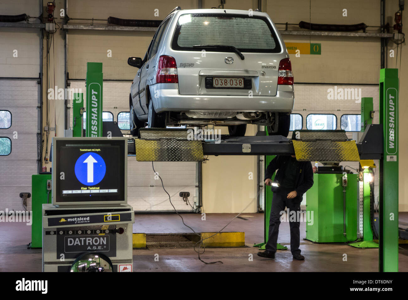 Inspector examining car on ramp in MOT testing centre for a yearly motor vehicle inspection - Stock Image
