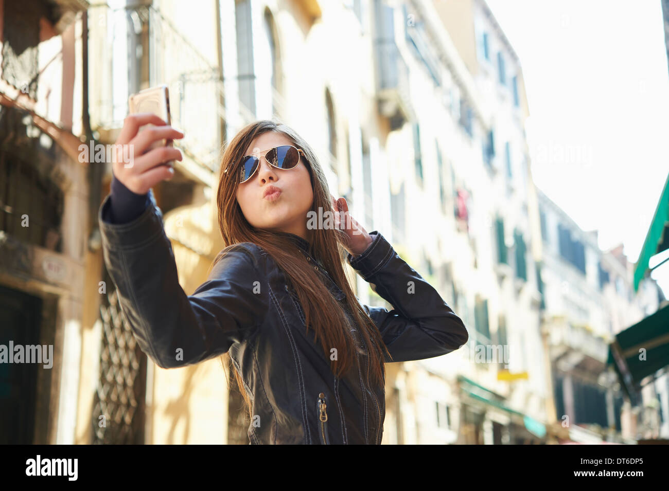 Girl taking selfie on smartphone, Venice, Italy - Stock Image