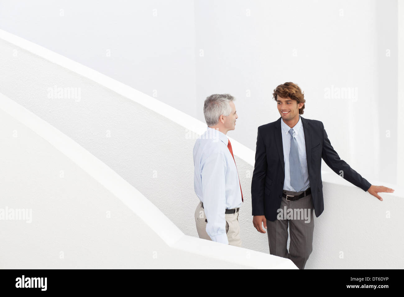 Business colleagues holding meeting on stairs - Stock Image