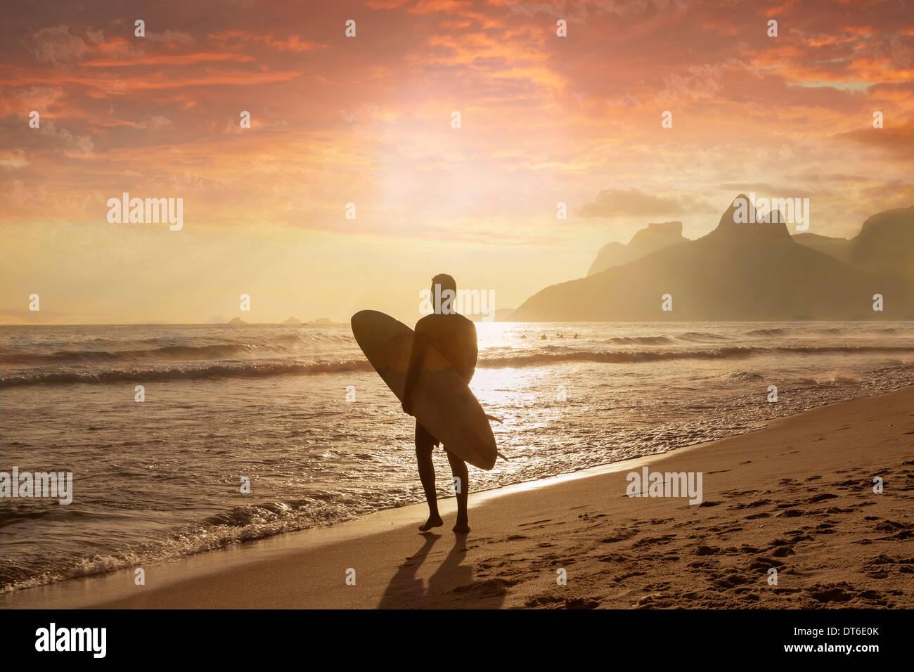 Young man carrying surfboard on Ipanema beach, Rio De Janeiro, Brazil - Stock Image
