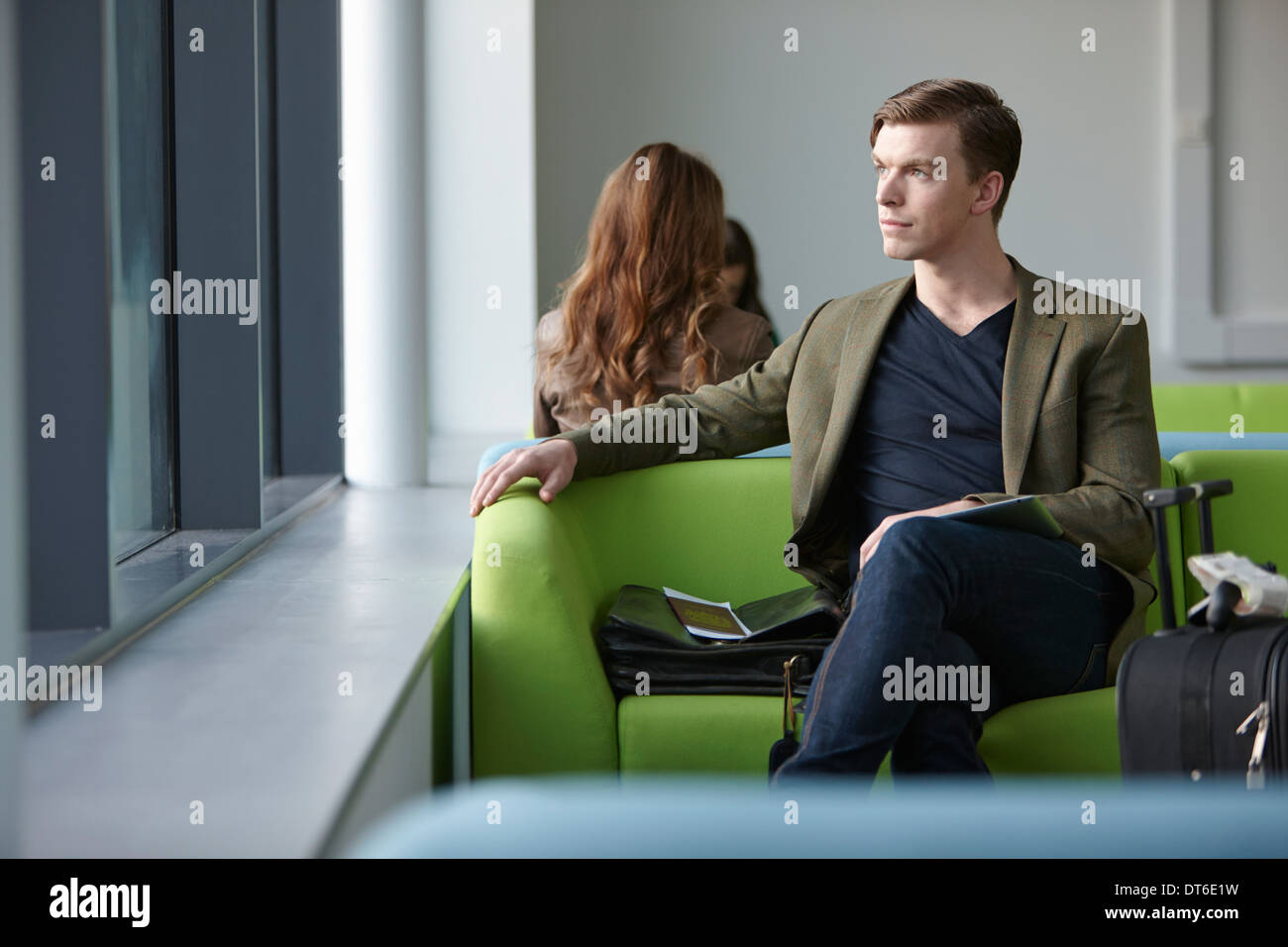 Young man in departure lounge - Stock Image