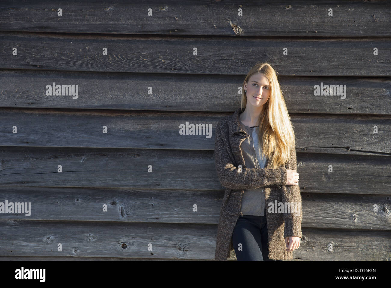 A young woman leaning against the wooden wall of a barn wearing a long knitted coat. Stock Photo