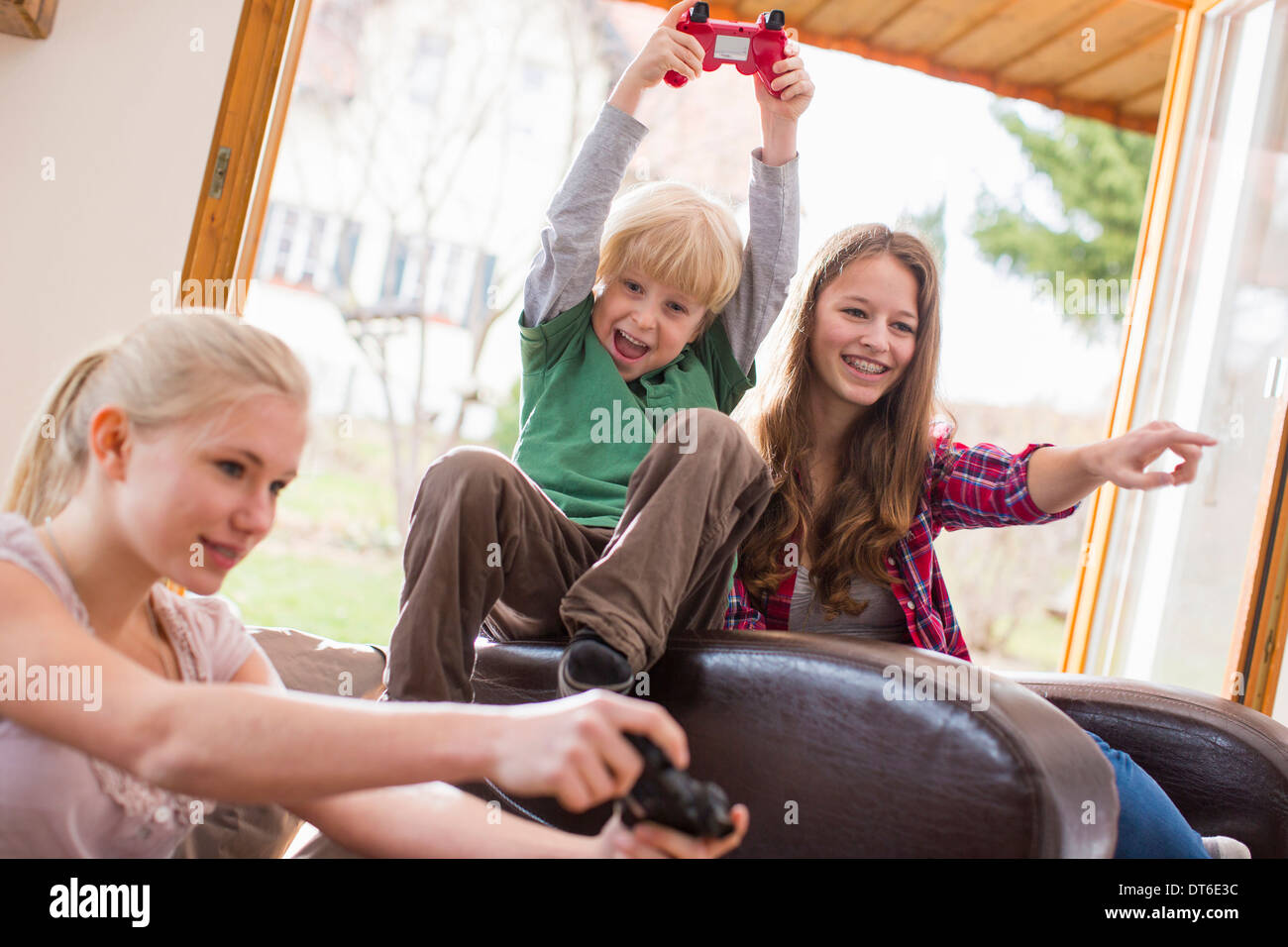 Teenage girls and boy playing games console - Stock Image