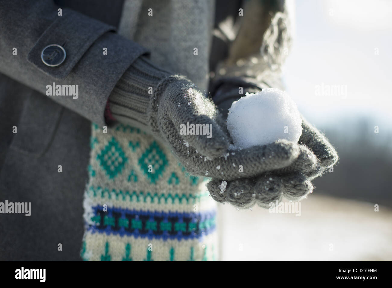 A young woman holding a small snowball in her gloved hands. - Stock Image