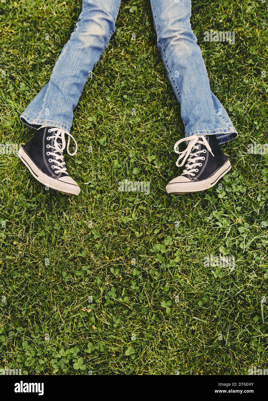A ten year old girl lying on the grass. Cropped view of her lower legs. Wearing sneakers and faded blue jeans. - Stock Image