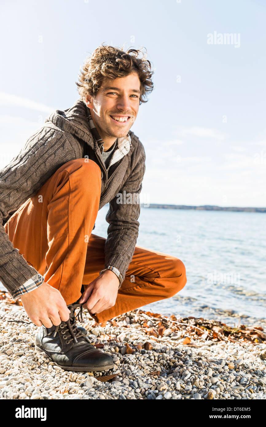 Man tying shoelace on lakeshore - Stock Image