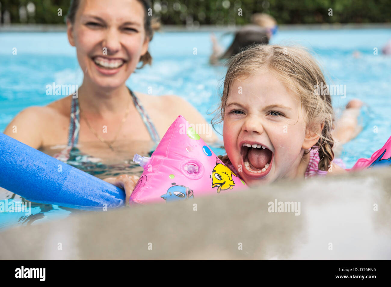 Mother and child having fun in pool - Stock Image