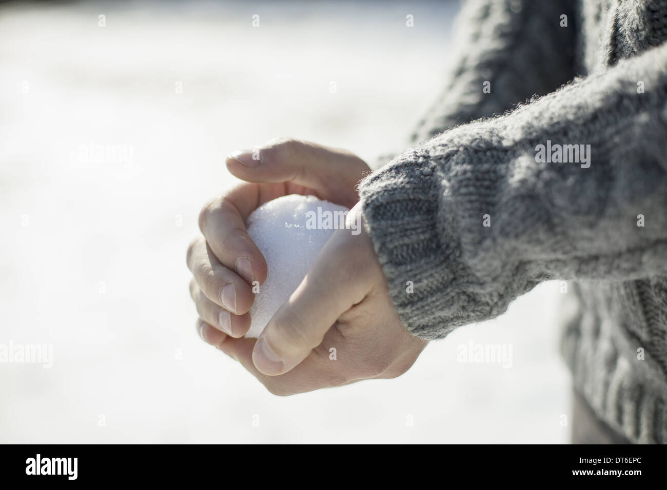A man holding a large snowball in his bare hands. - Stock Image